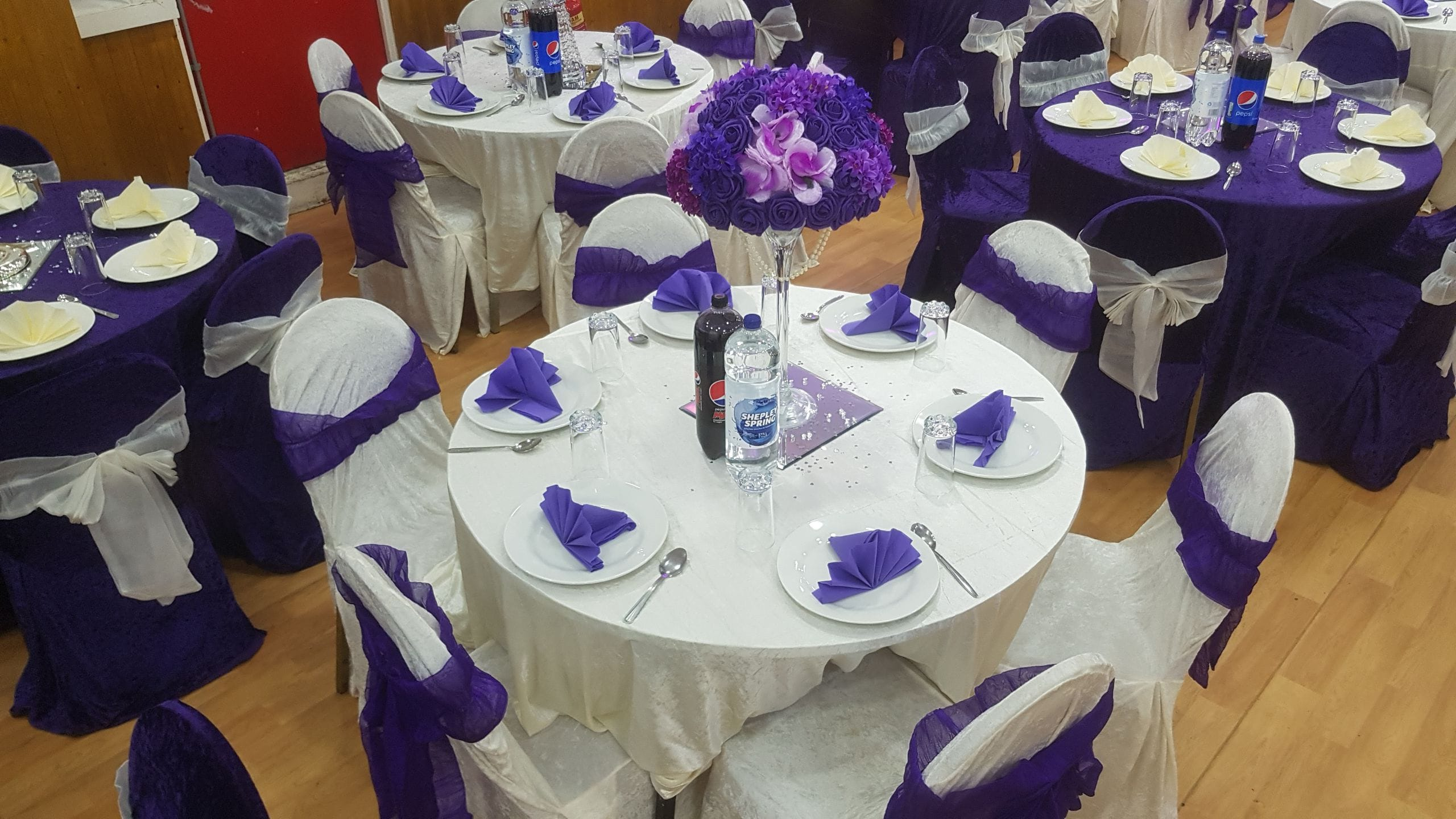A beautiful purple decoration with a gold package and a floral ceramic centerpiece.